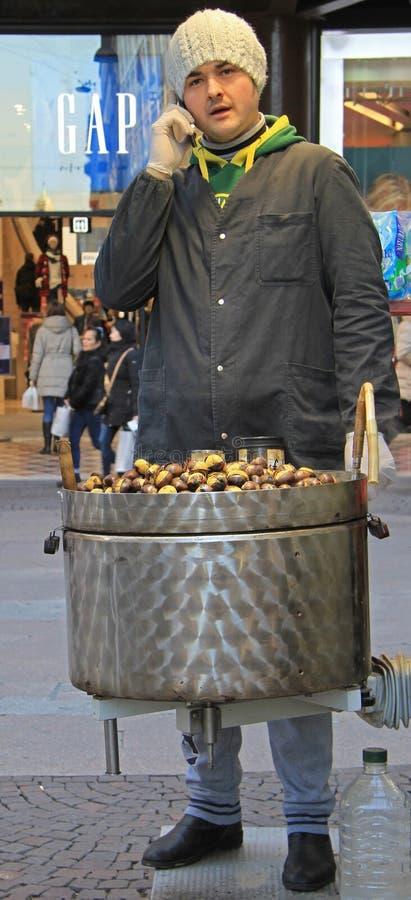 El hombre está vendiendo las castañas en la calle en Milán imágenes de archivo libres de regalías