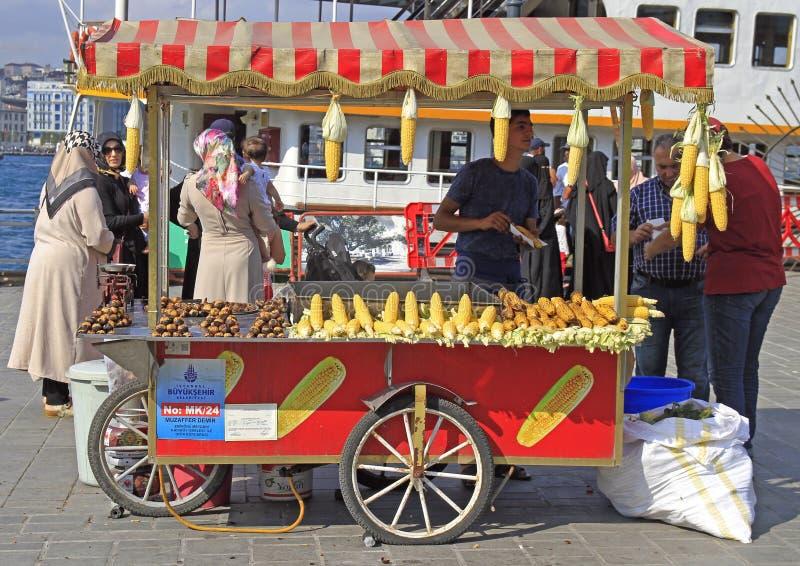 El hombre está vendiendo maíz frito y la castaña al aire libre en Estambul imagenes de archivo