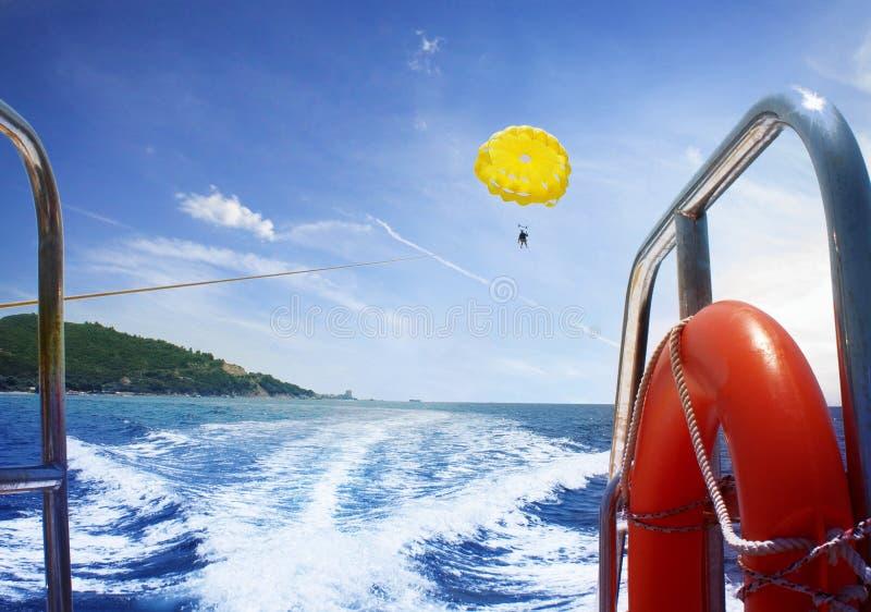 El hombre está volando en un ala flexible en el mar de un barco fotografía de archivo