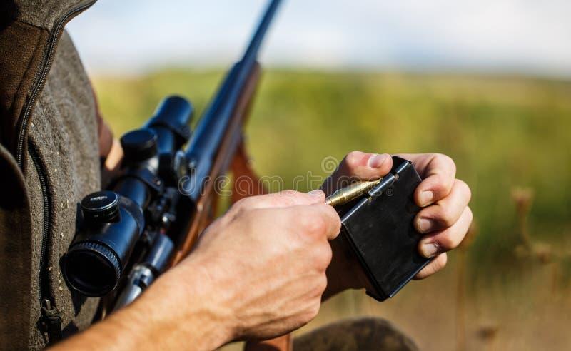 El hombre est? cargando un rifle de la caza Cazador masculino en listo para cazar primer Munici?n con un arma, cartuchos Hombre d foto de archivo libre de regalías