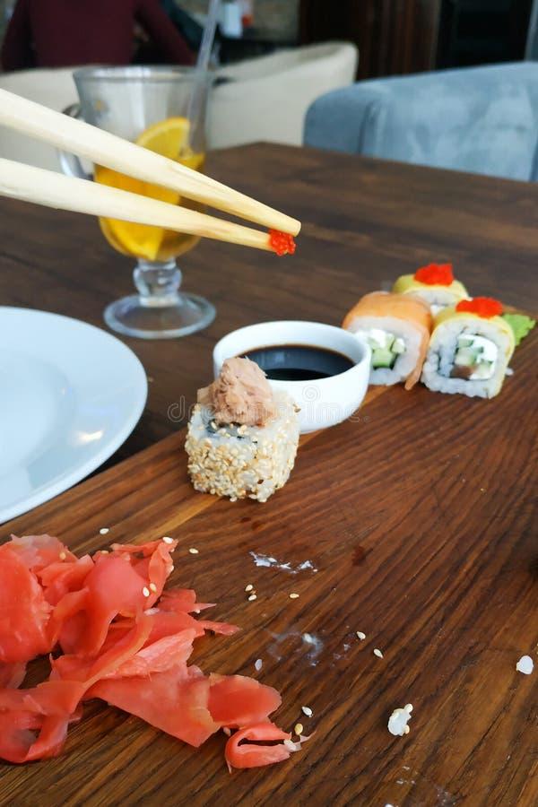 El hombre est? comiendo el sushi en la placa negra en una tabla de madera, primer de Rolls imágenes de archivo libres de regalías