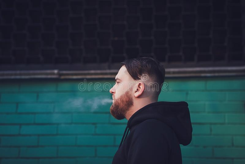 El hombre exhala humo del cigarrillo imagen de archivo libre de regalías
