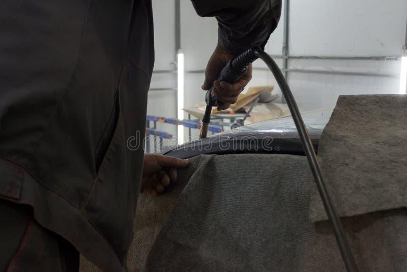 El hombre experimentado realiza el trabajo sobre el coche de la reparación del cuerpo con una soldadora fotos de archivo