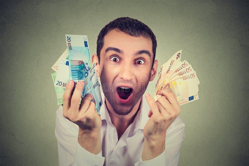El hombre feliz con los billetes de banco euro del dinero extáticos celebra éxito imagen de archivo