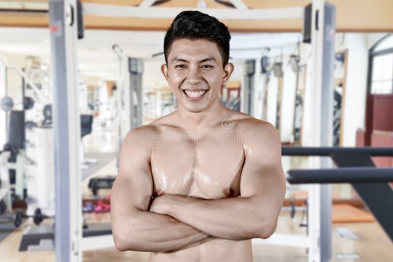 El hombre feliz dobló sus brazos en centro del gimnasio imagenes de archivo