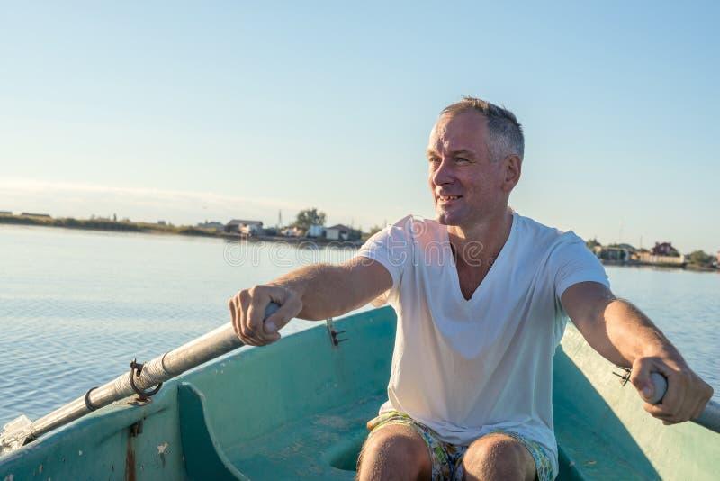 El hombre feliz está remando en un bote pequeño fotografía de archivo
