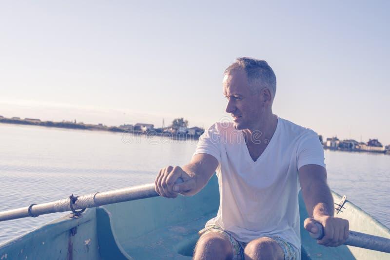 El hombre feliz está remando en un bote pequeño y un sueño imagen de archivo libre de regalías