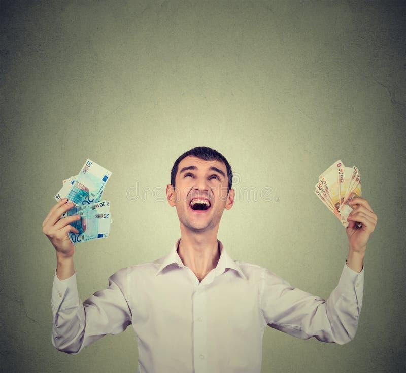 El hombre feliz extático celebra el éxito que sostiene billetes de banco de las cuentas del euro del dinero imagenes de archivo