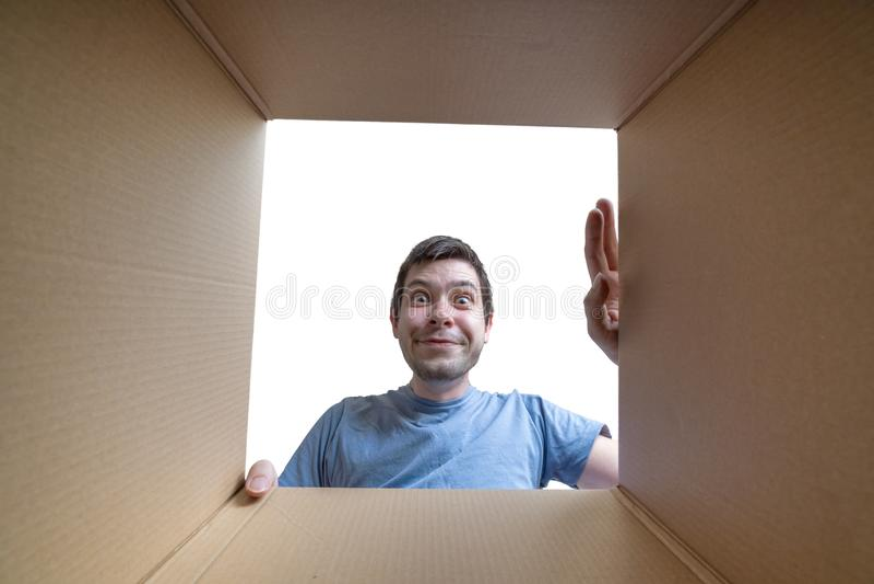 El hombre feliz joven está abriendo el regalo y está mirando la caja de cartón interior foto de archivo