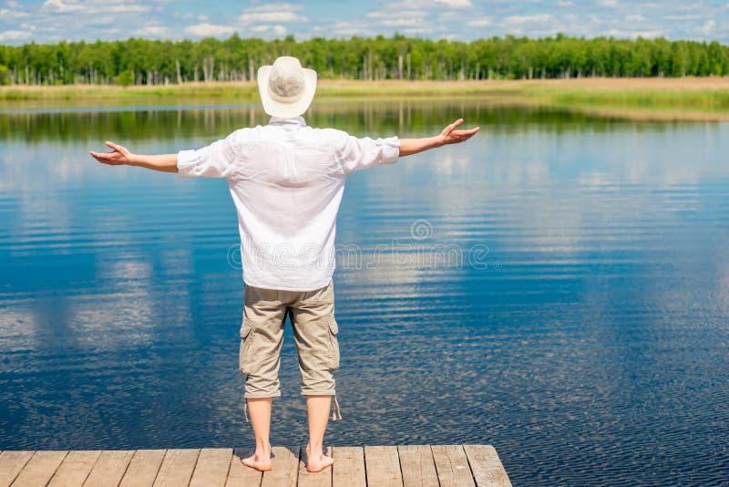 El hombre feliz libre disfruta de la naturaleza hermosa cerca del lago imagen de archivo libre de regalías