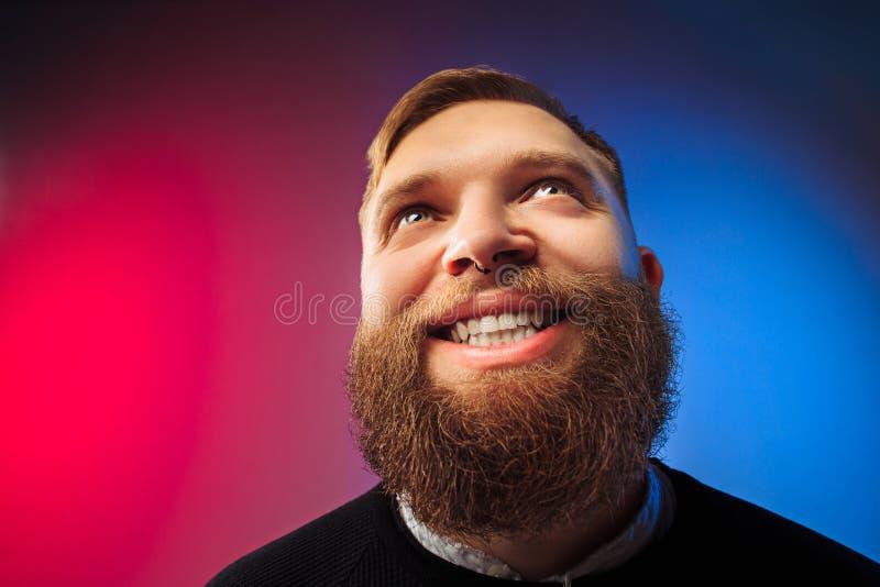 El hombre feliz que se opone y que sonríe contra fondo rosado imagen de archivo