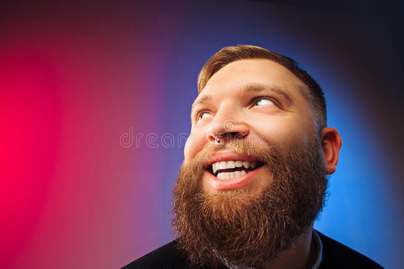 El hombre feliz que se opone y que sonríe contra fondo rosado imágenes de archivo libres de regalías