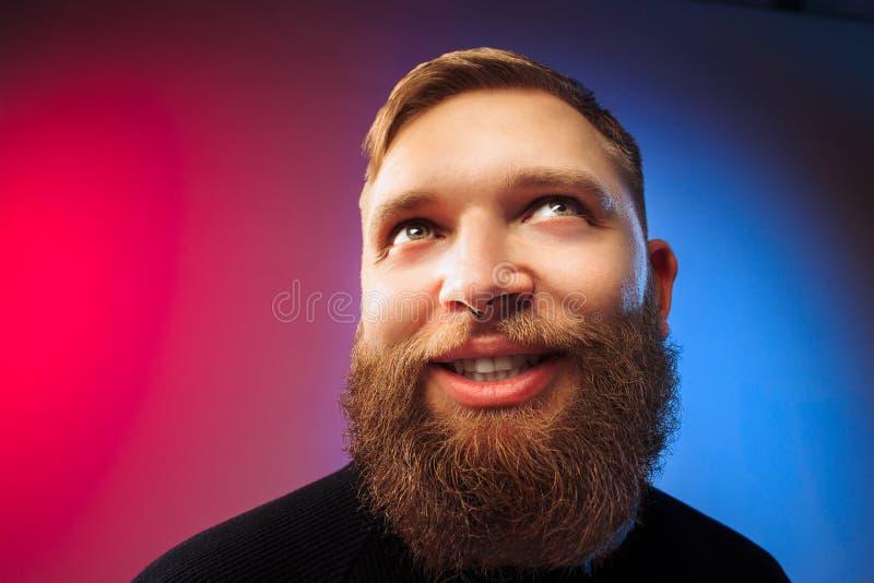 El hombre feliz que se opone y que sonríe contra fondo rosado fotos de archivo