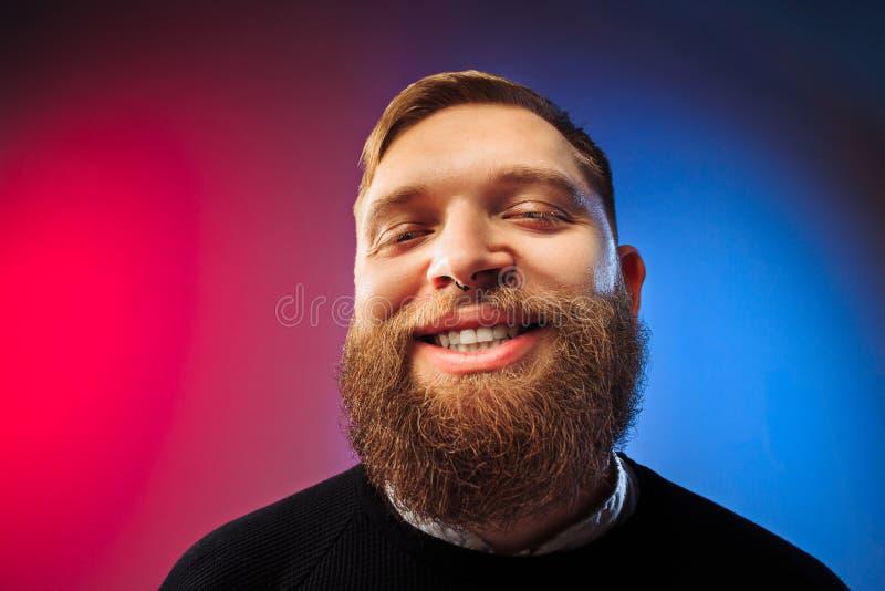 El hombre feliz que se opone y que sonríe contra fondo rosado foto de archivo