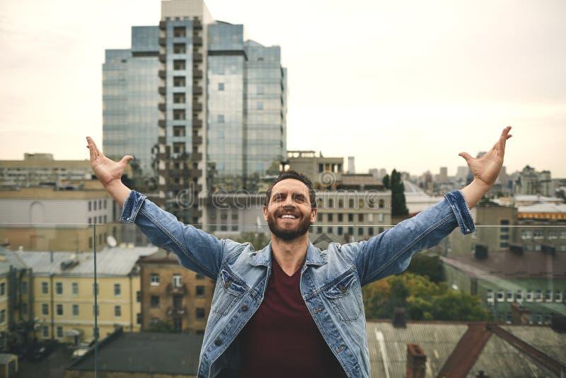 El hombre feliz se está colocando en terraza hermosa imagen de archivo