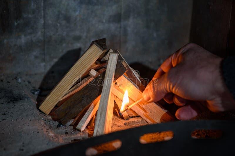 El hombre fija el fuego a la madera en el horno imagen de archivo