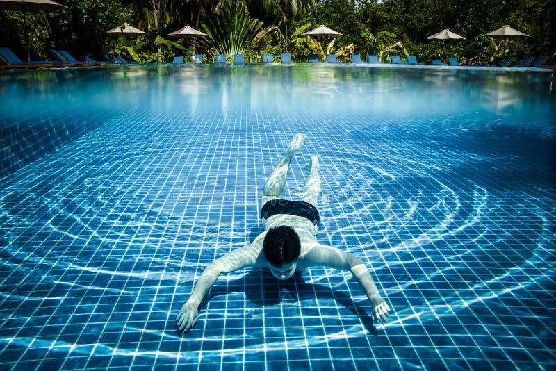 El hombre flota bajo el agua en piscina imagen de archivo libre de regalías