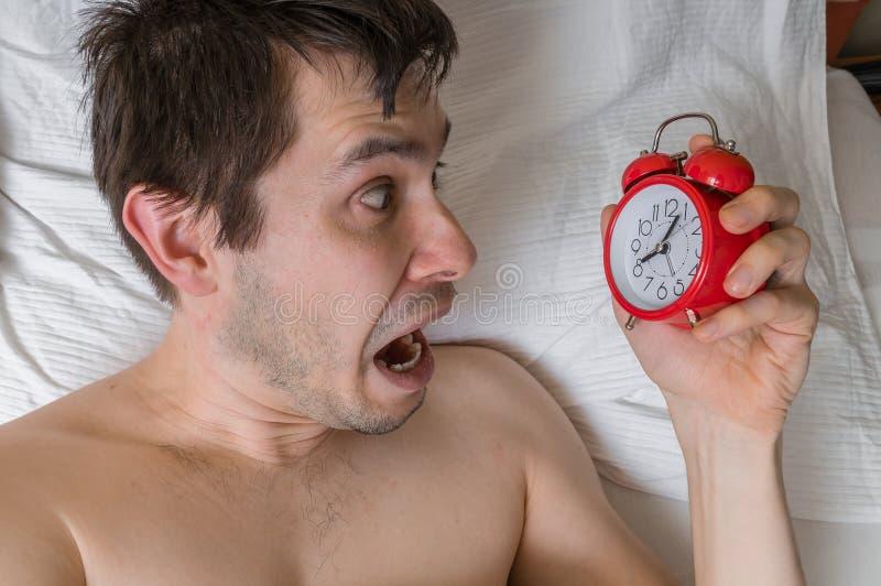 El hombre frustrado y subrayado de los jóvenes es atrasado Él es el despertar, mirando el despertador imagenes de archivo