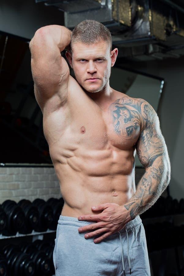 El hombre fuerte descamisado muscular con los ojos azules y el tatuaje presenta en pantalones de un gris en un gimnasio fotos de archivo libres de regalías