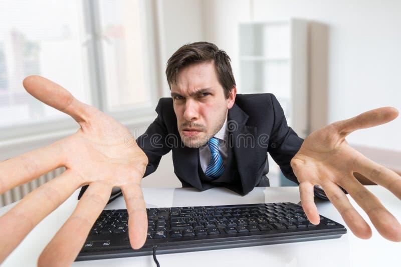 El hombre furioso y confuso subrayado está trabajando con el ordenador fotos de archivo libres de regalías