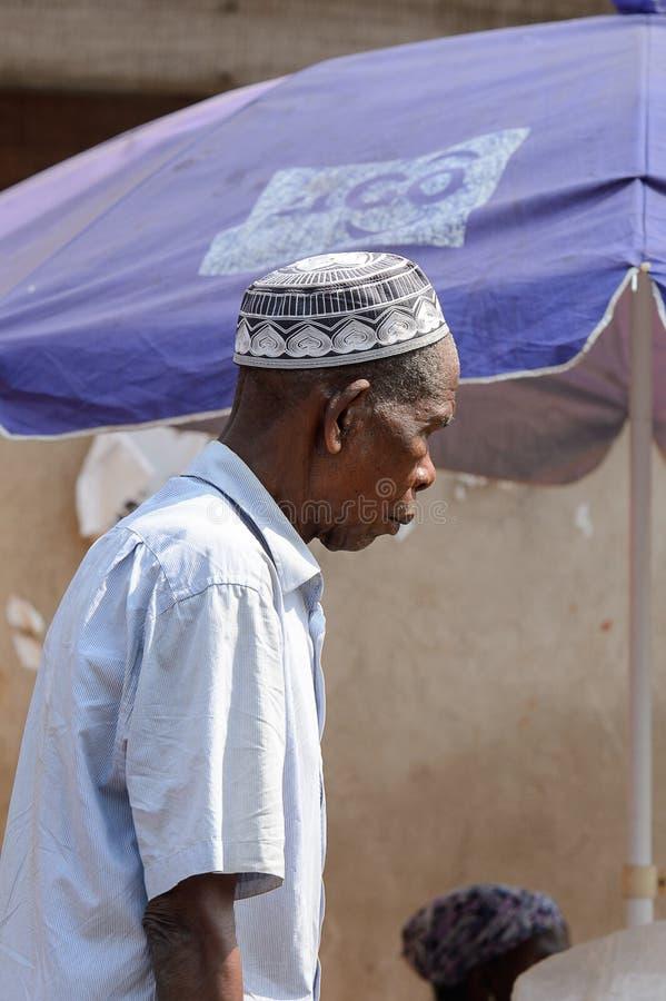 El hombre ghanés no identificado en la camisa y el skullcap blancos mira el dow fotografía de archivo