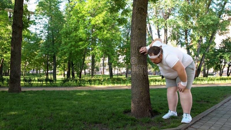 El hombre gordo cansó después de correr en el parque, inclinándose en árbol, los entrenamientos pesados al aire libre fotografía de archivo