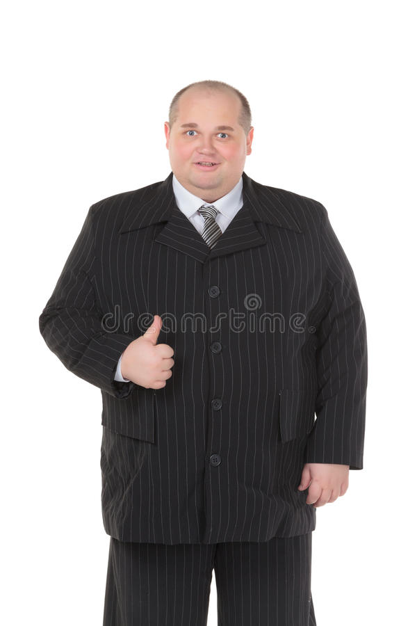 El hombre gordo elegante en un juego negro muestra el pulgar-para arriba fotografía de archivo