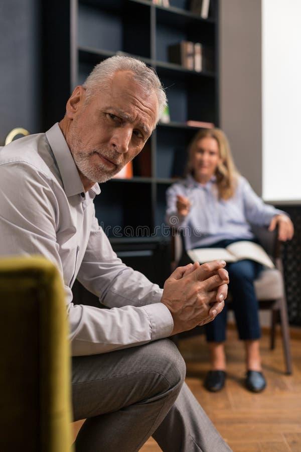 El hombre gris-cabelludo triste serio con sus fingeres cruzó imágenes de archivo libres de regalías