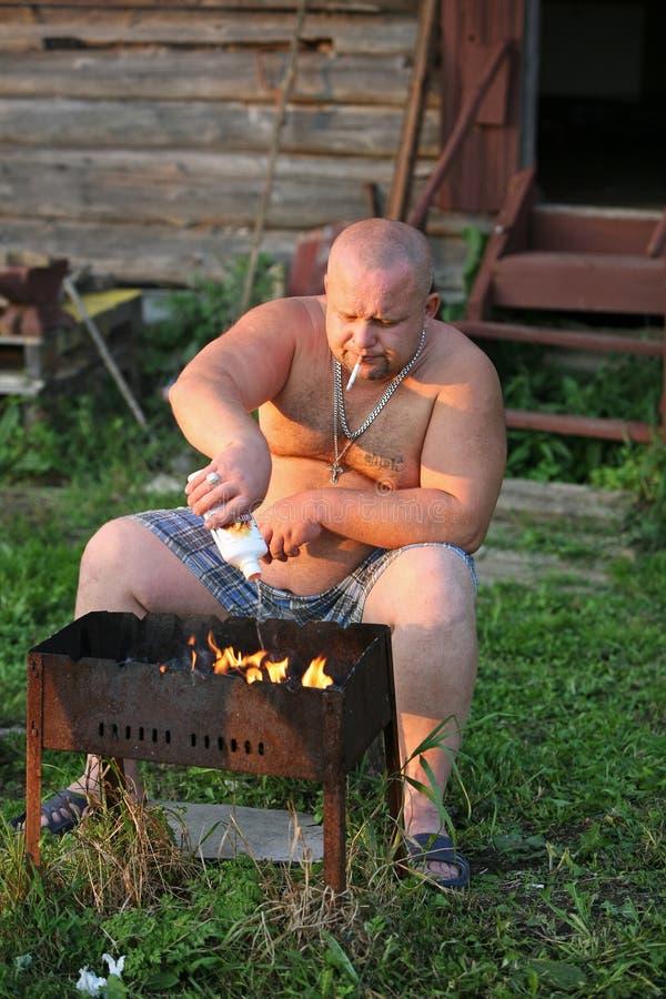 El hombre hace el fuego fotografía de archivo