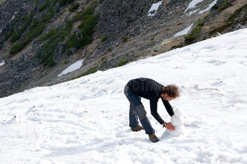 El hombre hace el muñeco de nieve foto de archivo
