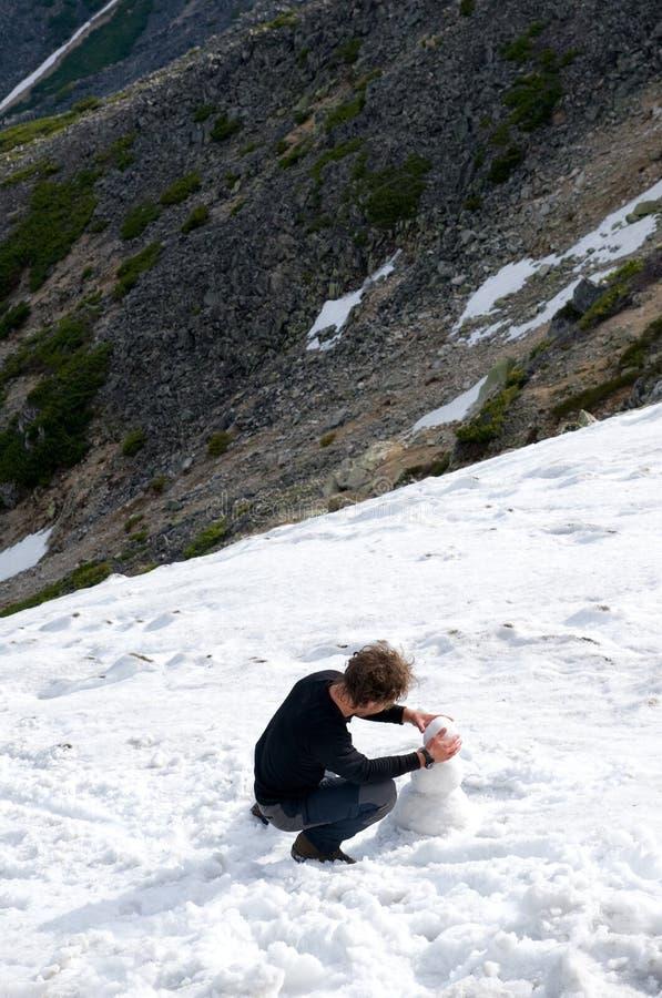 El hombre hace el muñeco de nieve fotografía de archivo libre de regalías