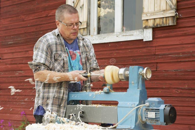 El hombre hace el trabajo del carpintero fuera de su casa en Korpilahti, Finlandia fotos de archivo libres de regalías