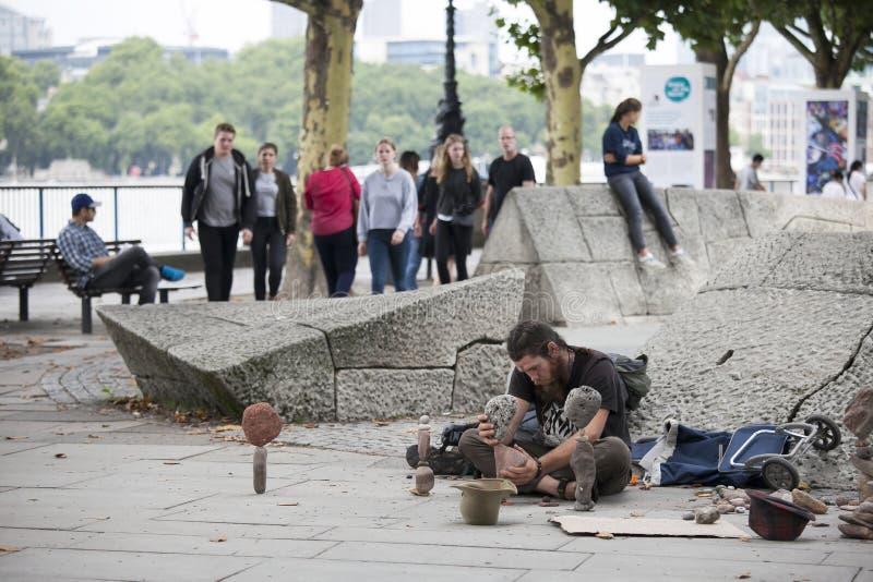 El hombre hace esculturas de piedras en la costa fotos de archivo libres de regalías