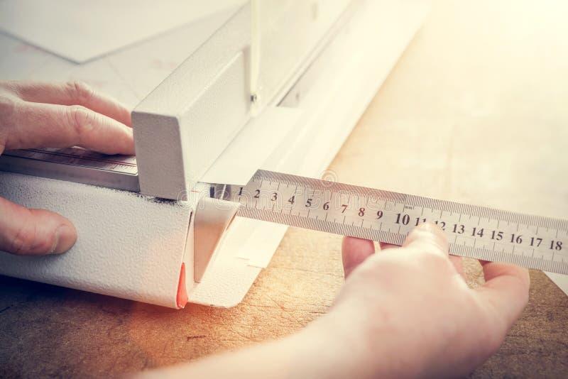 El hombre hace la medición con el calibrador de diapositiva en el cortador de papel fotografía de archivo