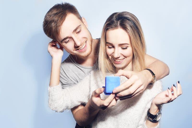El hombre hace el presente a su muchacha preciosa del amor Hombre joven que da un regalo Junte el ofrecimiento el uno al otro de  fotos de archivo