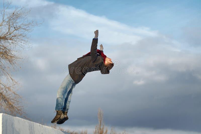 El hombre hace salto mortal hacia atrás foto de archivo