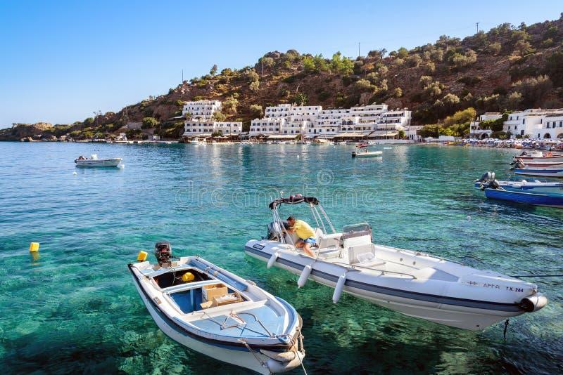 El hombre hace un repeir de la motora en la bahía de la ciudad de Loutro en la isla de Creta foto de archivo