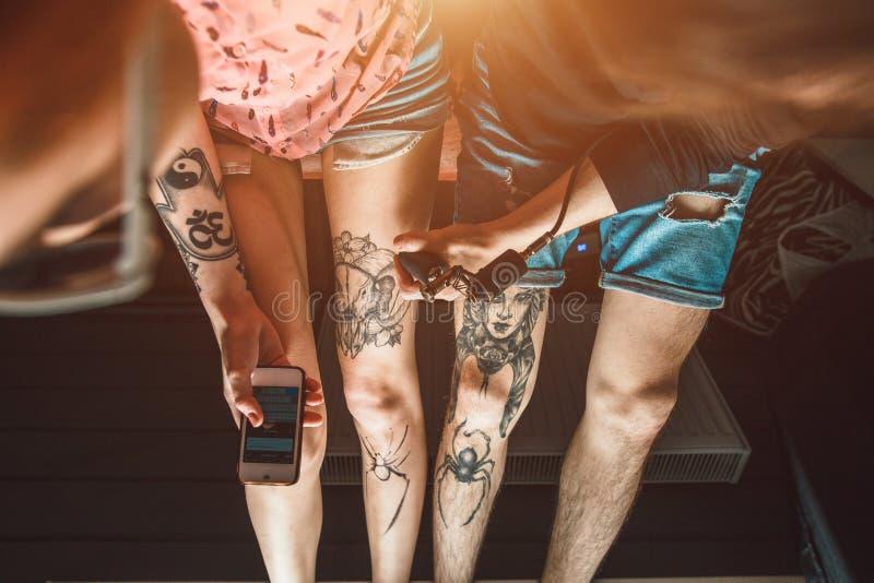 El hombre hace una muchacha un tatuaje imagenes de archivo