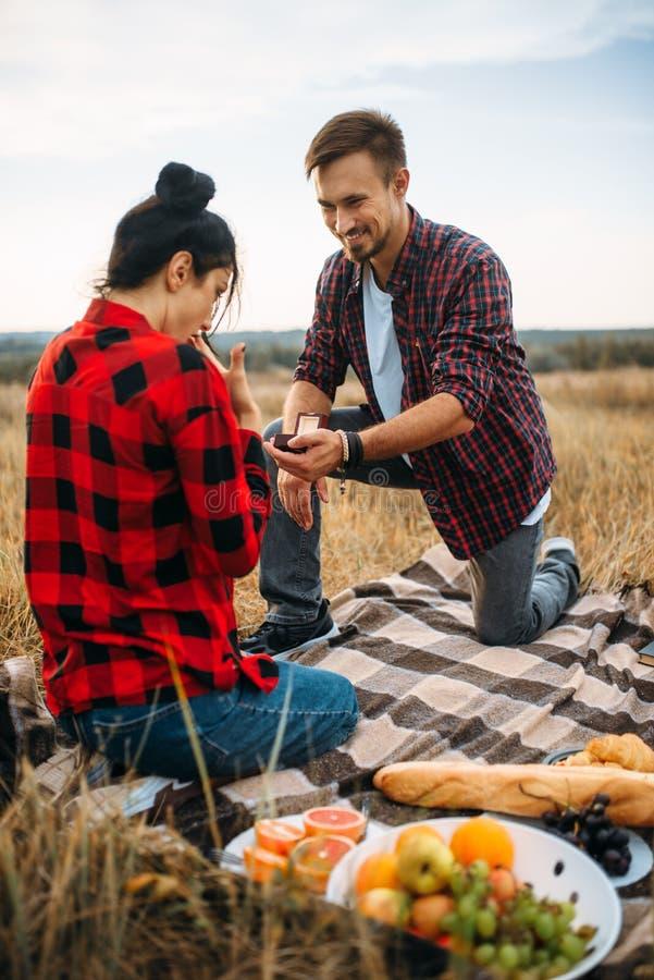 El hombre hace una propuesta de matrimonio en comida campestre romántica imagen de archivo