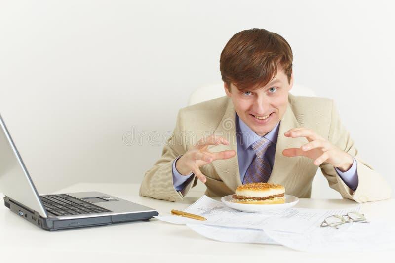El hombre hambriento joven va a comer un emparedado foto de archivo