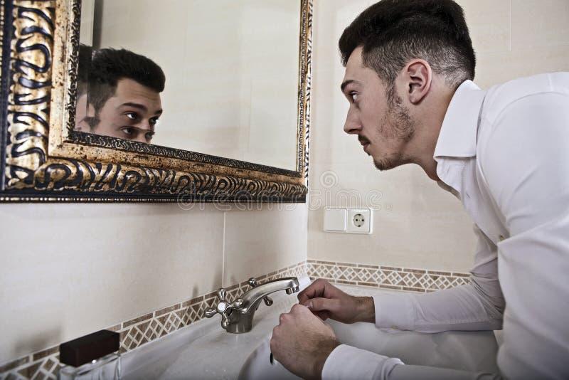 El hombre hecha una ojeada se en el espejo. imágenes de archivo libres de regalías