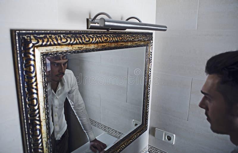 El hombre hecha una ojeada se en el espejo. fotografía de archivo