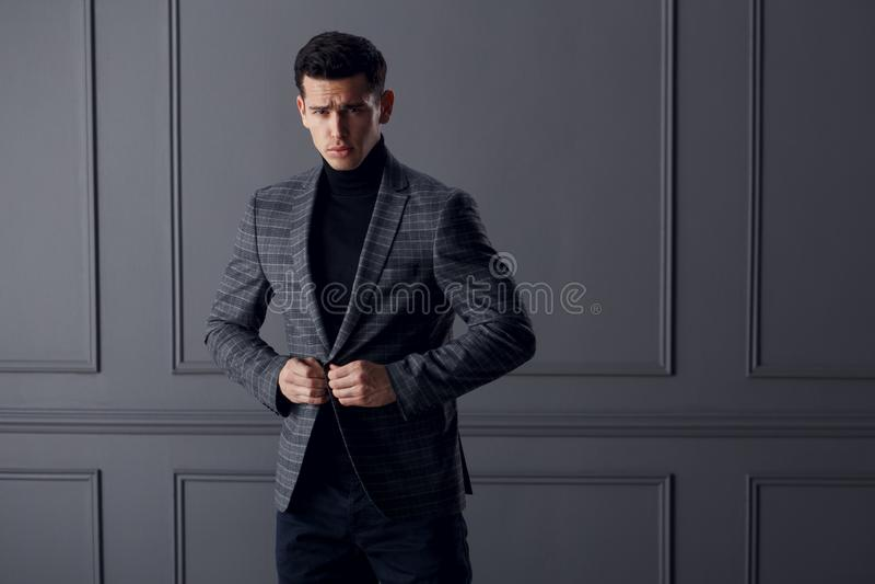 El hombre hermoso, apto en traje gris con el cuello alto negro, las lentes elegantes negras mira confiado la cámara imagen de archivo