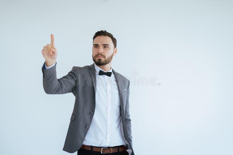 El hombre hermoso con barbudo en mano formal de la demostración del smoking y del traje que señala algo en el fondo blanco, copia fotografía de archivo