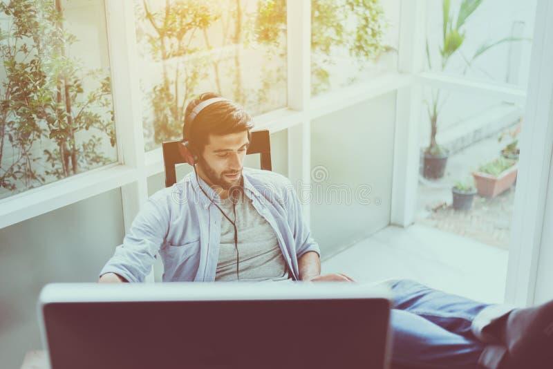 El hombre hermoso con el libro de lectura de la barba y el escuchar la música en línea en la sala de estar, feliz y la sonrisa, r imagen de archivo libre de regalías