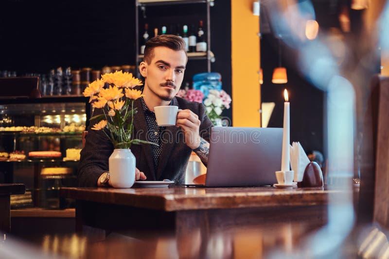 El hombre hermoso del freelancer con la barba y el pelo elegantes se vistió en un traje negro que se sentaba en un café con un or imágenes de archivo libres de regalías