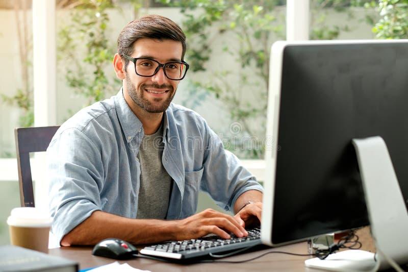 El hombre hermoso del ingeniero está mecanografiando el ordenador en la tabla en la oficina con la ventana de cristal foto de archivo libre de regalías