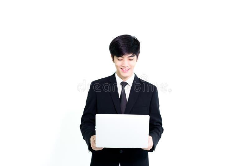 El hombre hermoso del negocio asiático tiene sostener el ordenador portátil para woking con feliz y relajarse aislado en el fondo imagen de archivo libre de regalías