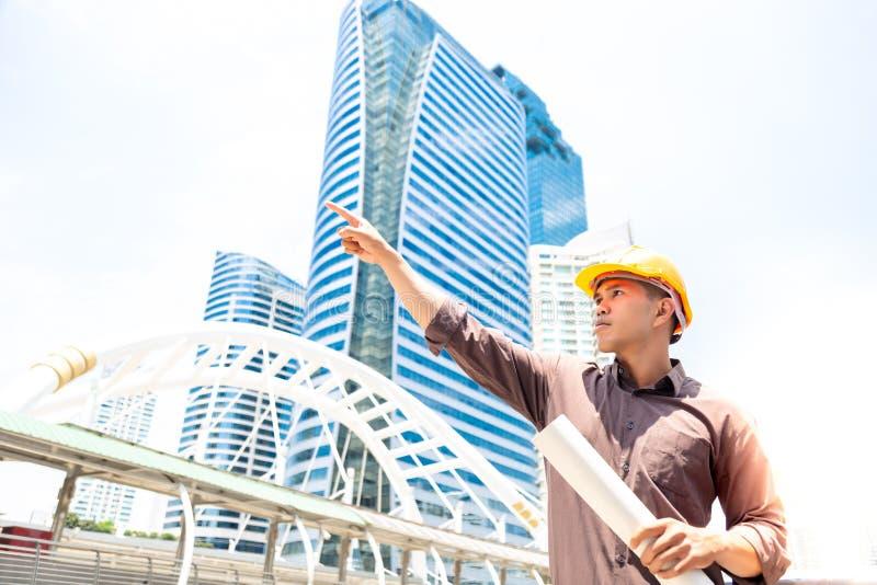 El hombre hermoso del trabajador o del ingeniero está señalando el finger, mirando a c fotografía de archivo