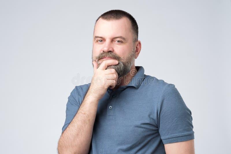 El hombre hermoso en camisa azul mira seriamente in camera y frota su barbilla foto de archivo libre de regalías